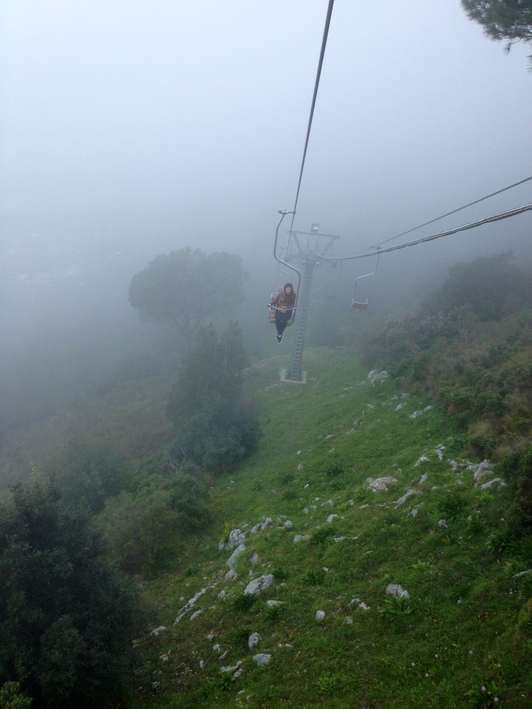 My friend as she trails behind me on the chair lift up Mt. Solaro.