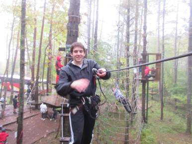 """After losing his balance, Gabe cheats a little and grabs hold onto the zip-line to complete this course. Meanwhile, in the background, I """"Tarzan swung"""" into a net."""