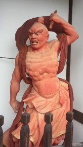 Agyou is the guardian with an open mouth, wielding a vajra, and is known as a symbol of overt violence.